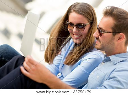 Happy couple on holidays staying in touch through a laptop