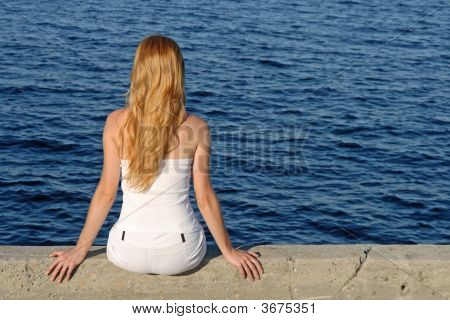 Longhaired Girl Sitting By The Sea
