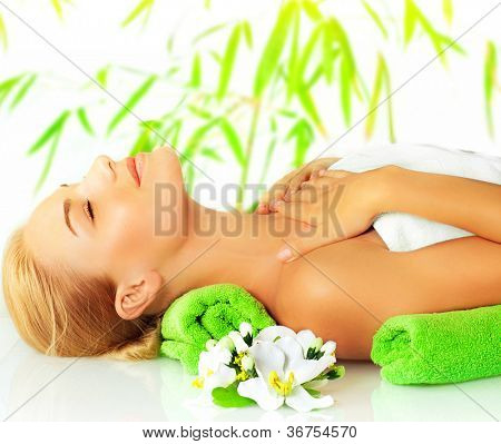 Closeup portrait of beautiful young lady in spa salon, attractive woman sleeping on massage table, side view of girl lying down with closed eyes enjoy dayspa, bamboo background and orchid flower