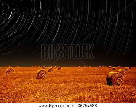 Picture of night landscape of farm field, starry sky above dry haystack on farmland, magic stars slow motion rotating above earth, autumn harvest season, starlight in night on cereal meadow