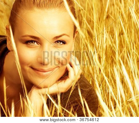 Picture of attractive smiling girl sitting in golden wheat field, closeup portrait of beautiful young blond female on yellow ryes background, enjoying countryside, autumn season of grain harvest