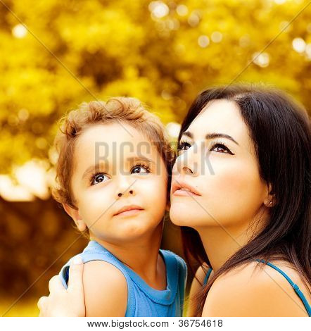 Image of cute baby boy hug his lovely mom in autumn park, closeup portrait of young arabic woman with son looking up on golden autumn background, happy family and love concept