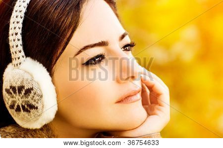 Photo of attractive woman, closeup portrait of brunette arabian girl with fashionable makeup on gold autumn background, beautiful female wear stylish clothes accessories for head, fall season