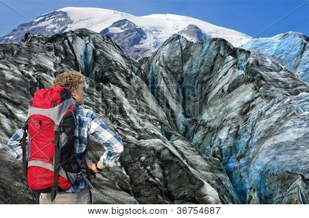 Hiker overlooking the huge crevasses and rugged terrain of the the glacier he's about to climb, absorbing the sheer challenge he's facing