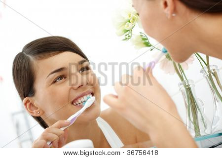 Image of pretty female brushing her teeth in front of mirror in the morning