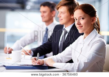 Three business people sitting at seminar with smiling woman at foreground