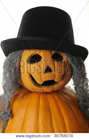 Closeup image of a pumpkin man with gray stringy hair and a top hat.  On a white background.