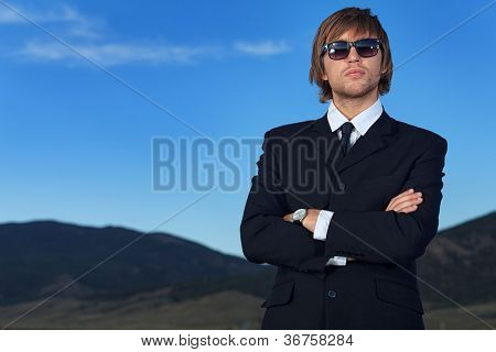 Handsome business man standing on a highway.