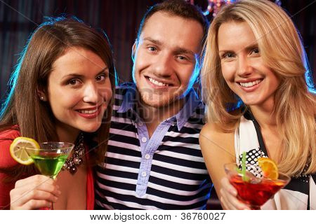Portrait of happy friends cheering up and looking at camera at party