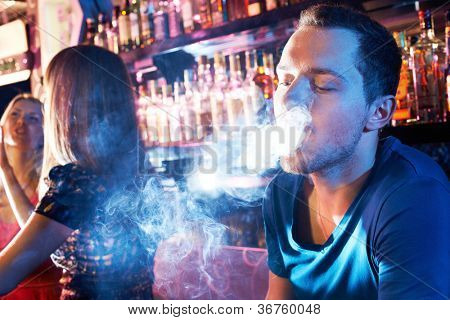 Portrait of young man letting smoke out of mouth while smoking hookah