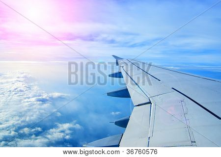 Wing of an airplane flying above the clouds. people look at the sky from the window of the plane, using air transport to travel. back light sun beam