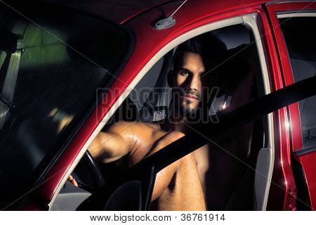 Portrait of a sexy young man sitting in car