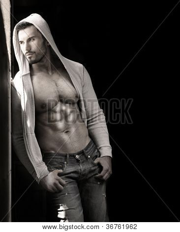 Young handsome macho man with open jacket revealing muscular chest and abs with copy space