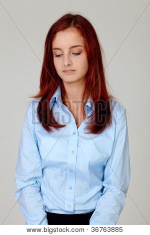 Portrait of attractive shy embarrassed businesswoman looking down in blue shirt, isolated on grey