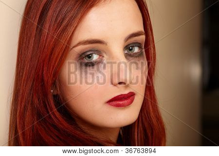 Beautiful attractive young crying girl in depression shoot against wall