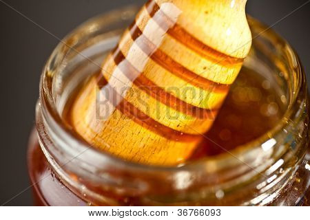 Honey dipper outgoing a jar against a black background