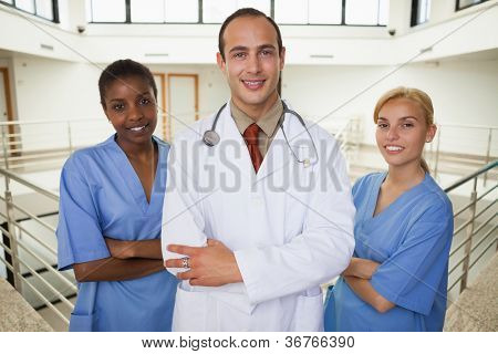 Smiling doctor and nurses looking at camera in hospital corridor