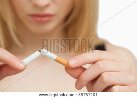 Serious woman breaking a cigarette against white background