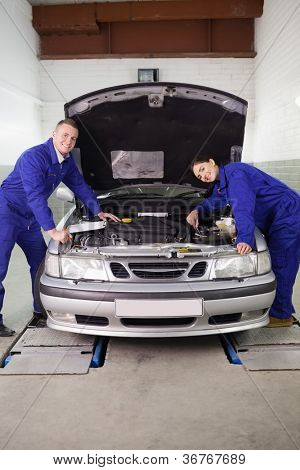 Mechanics smiling while leaning on a car in a garage