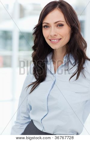 Young manager standing upright in front of the window while smiling