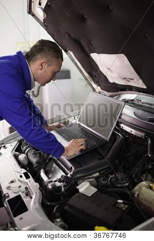 Mechanic looking at a computer on a car engine in a garage