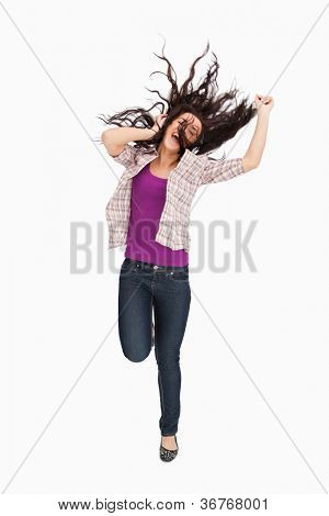 Brunette jumping with her hair in the air against white background