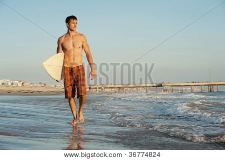 Active Young Surfer Holding A Surfboard