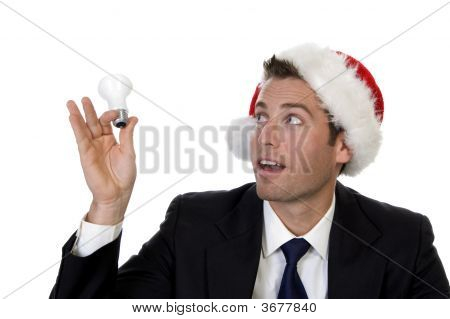 Businessman Looking Bulb And Wearing Santacap