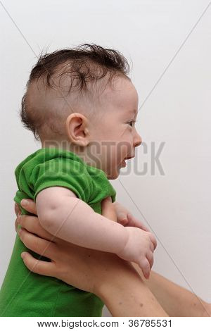 Cute smiling baby held by his mother profile view