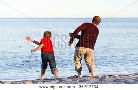 Father and son throwing pebbles into the sea