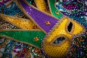 stock photo of carnivale  - A yellow Mardi Gras jester mask and beads - JPG