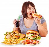 stock photo of beef-burger  - Overweight woman eating fast food - JPG