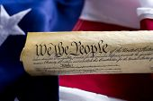 stock photo of the united states america  - A copy of the United States of America Constitution scroll in front of a large American Flag focus is on the word people - JPG