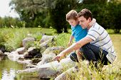 stock photo of water animal  - Father and son playing near park lake - JPG