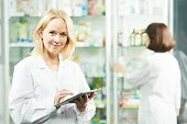 Cheerful happy pharmacist chemist woman working in pharmacy drugstore with tablet computer