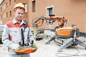 picture of millwright  - builder worker in safety protective equipment operating construction demolition machine robot - JPG