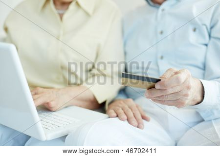 Senior couple hands with credit card and laptop during shopping through Internet