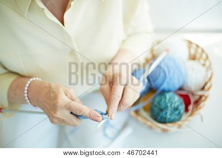 Hands of elderly woman knitting woolen clothes