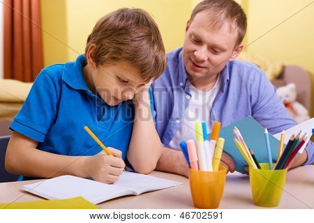Portrait of cute schoolboy and his father making schoolwork at home