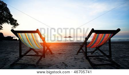 Couple of beach chairs on the evening sea coast