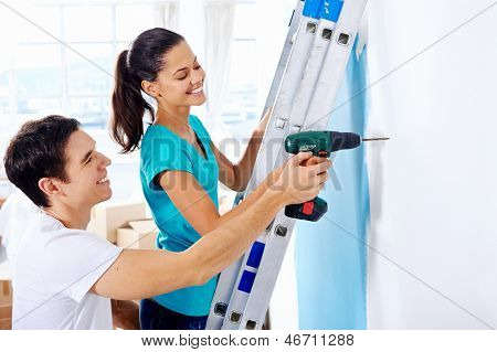 couple drilling in wall doing diy at new home after moving in together