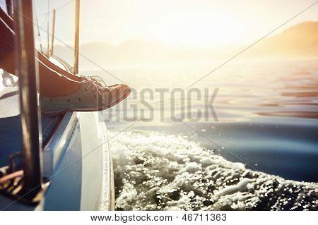 pies en el barco que navega en el estilo de vida de sunrise