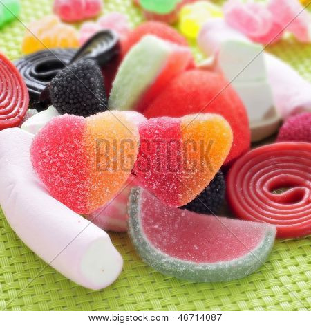 closeup of a pile of different candies on a green woven background