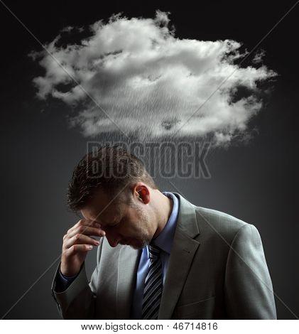 Stress, depression and despair - gloomy storm cloud raining above a businesmans head