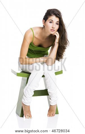 Beautiful young woman sitting in a green chair and waiting