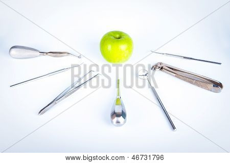 Dentist Tools In Front Of Green Apple
