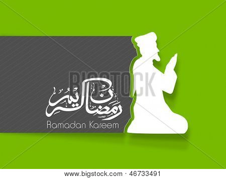 Arabic Islamic calligraphy of text Ramadan Kareem with white silhouette of a Muslim man in traditional dress praying (reading namaz, Islamic Prayer) on grey and green background.