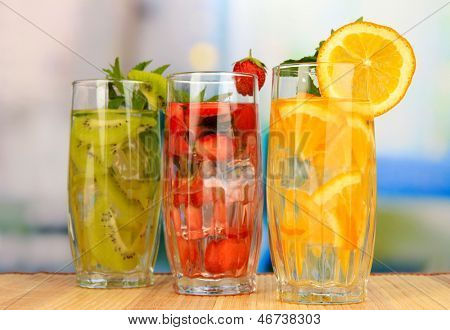 Glasses of fruit drinks with ice cubes on table in cafe