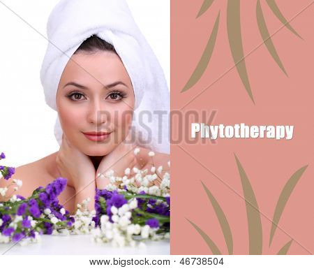 Beautiful young woman with towel on her head and flowers isolated on white
