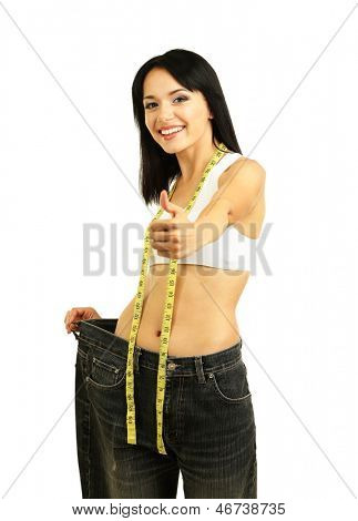 Beautiful young woman with big jeans and measuring tape isolated on white